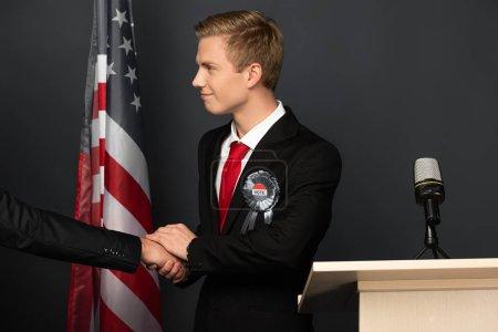 Photo pour Homme souriant serrant la main sur tribune avec drapeau américain sur fond noir - image libre de droit