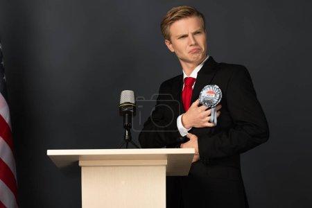 Photo pour Homme émotionnel touchant insigne sur tribune sur fond noir - image libre de droit