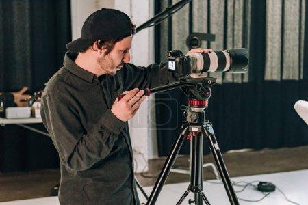 Photo pour Vue latérale d'un caméraman travaillant en studio de photographie - image libre de droit