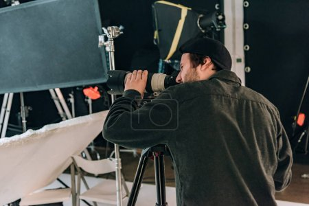 Photo for Side view of videographer with camera and reflectors at background - Royalty Free Image