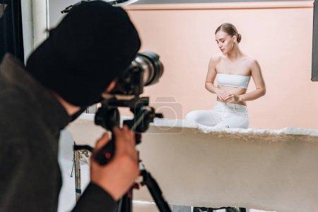 Photo pour Focus sélectif de belle femme posant pour vidéaste en studio photo - image libre de droit