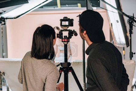 Photo pour Vue arrière du caméraman et de l'assistant regardant l'affichage de la caméra tout en travaillant avec une femme dans un studio photo - image libre de droit