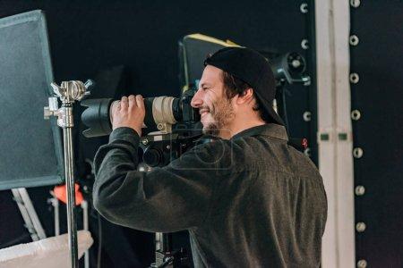 Photo pour Vue latérale d'un beau caméraman souriant travaillant dans un studio photo - image libre de droit