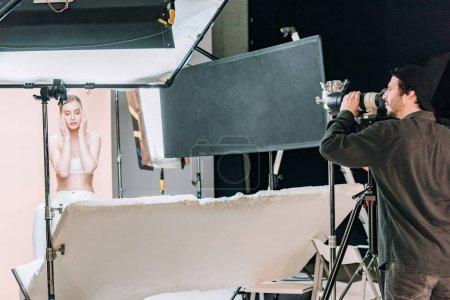 Photo pour Vidéographe travaillant avec une belle femme en studio de photographie - image libre de droit