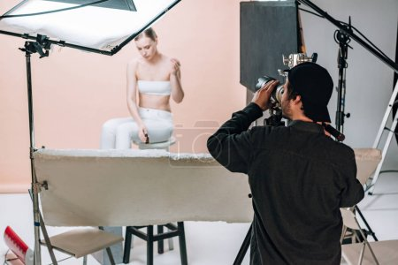 Photo for Videographer with camera filming beautiful model in photo studio - Royalty Free Image