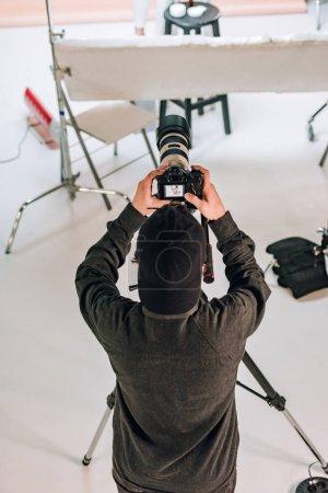 Photo pour Vue aérienne du caméraman regardant l'affichage de la caméra dans le studio photo - image libre de droit