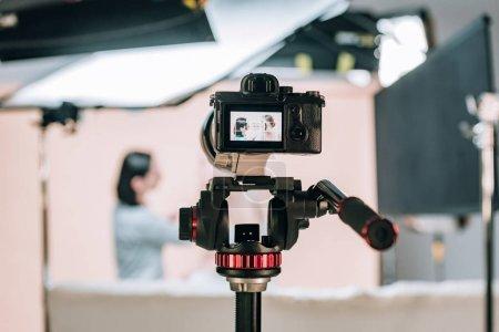 Photo pour Concentration sélective du modèle féminin et assistant réfléchissant dans l'affichage de la caméra dans le studio photo - image libre de droit