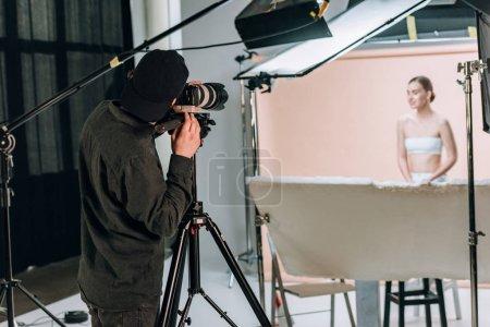 Photo pour Mise au point sélective du vidéaste filmant beau modèle féminin en studio photo - image libre de droit