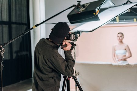 Photo for Selective focus of cameraman working with beautiful model in photo studio - Royalty Free Image