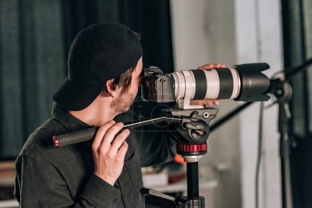 Photo for Side view of handsome videographer with camera on tripod in photo studio - Royalty Free Image