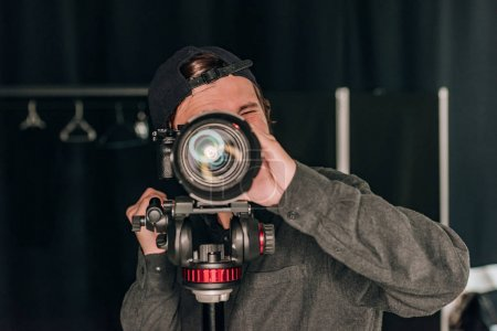 Photo for Videographer looking through camera while working in photo studio - Royalty Free Image