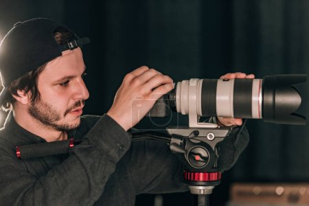 Photo pour Vue latérale d'un vidéographe regardant une caméra pendant qu'il travaillait dans un studio de photographie - image libre de droit