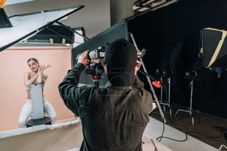 Photo for Beautiful smiling model posing to videographer with camera in photo studio - Royalty Free Image