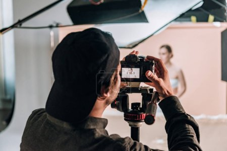 Photo for Selective focus of videographer with camera working with beautiful woman in photo studio - Royalty Free Image