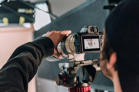 Photo pour Focus sélectif du vidéaste filmant une femme en studio photo - image libre de droit