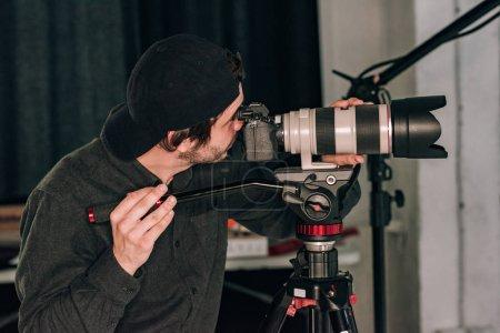 Photo pour Vue latérale d'un vidéographe travaillant avec un appareil photo dans un studio de photographie - image libre de droit