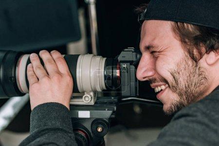 Photo pour Vue latérale du beau vidéaste souriant avec caméra - image libre de droit