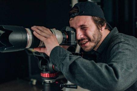 Photo pour Vidéographe avec appareil photo travaillant dans un studio de photographie - image libre de droit