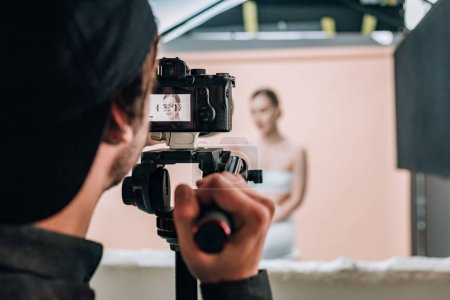 Photo for Selective focus of videographer looking at camera display while working with model - Royalty Free Image