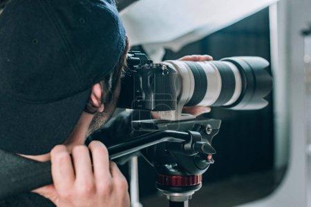 Photo pour Mise au point sélective de l'opérateur avec caméra travaillant en studio photo - image libre de droit