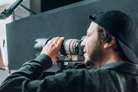 Photo pour Vue latérale d'un beau caméraman travaillant en studio de photographie - image libre de droit