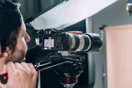 Photo pour Focus sélectif d'un vidéographe filmant une belle femme en studio photo - image libre de droit