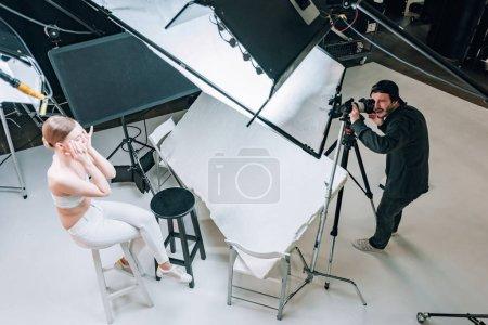 Photo pour Vue aérienne du beau mannequin et vidéaste travaillant dans un studio photo avec projecteurs - image libre de droit