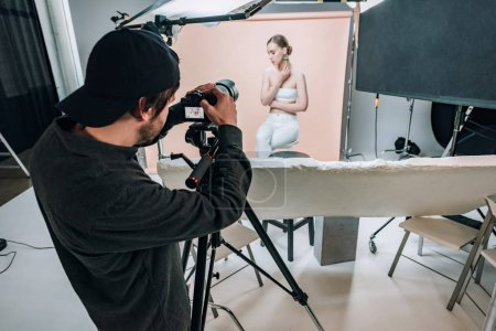 Cameraman looking at camera display while filming attractive model in photo studio