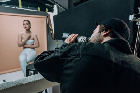 Photo for Selective focus of videographer filming female model in photo studio - Royalty Free Image