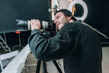 Photo pour Vue latérale du vidéaste avec caméra sur trépied en studio photo - image libre de droit