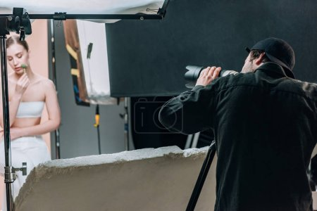 Photo pour Mise au point sélective du caméraman et modèle attrayant avec rouleau de massage en studio photo avec projecteurs - image libre de droit