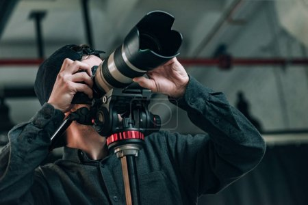 Photo pour Vue à faible angle du vidéographe avec caméra sur trépied en studio de photographie - image libre de droit