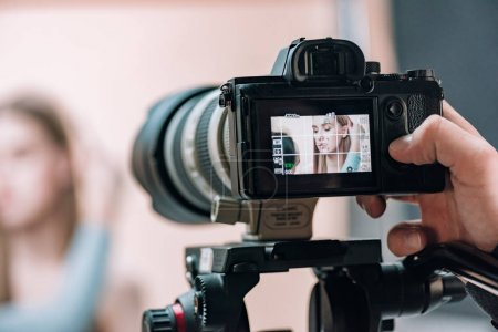 Photo pour Mise au point sélective du beau modèle sur l'écran de la caméra dans le studio photo - image libre de droit