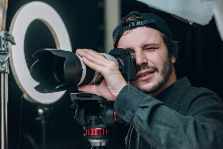Photo pour Vidéographe regardant un viseur d'appareil photo en studio - image libre de droit