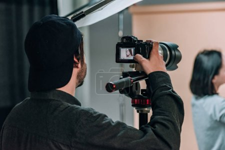 Photo for Rear view of videographer with assistant and model working in photo studio - Royalty Free Image