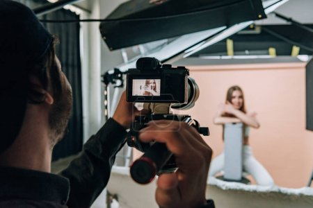 Photo for Over shoulder view of videographer filming beautiful model in photo studio - Royalty Free Image
