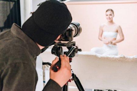 Photo pour Selective focus of cameraman shooting smiling model in photo studio - image libre de droit