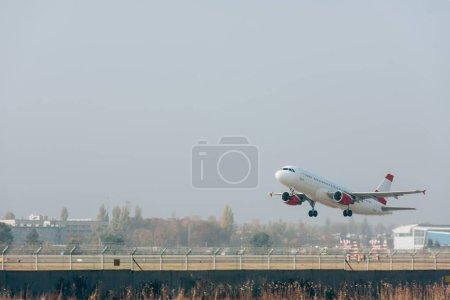 Photo pour Avion jet au-dessus de la piste de l'aéroport avec ciel nuageux en arrière-plan - image libre de droit