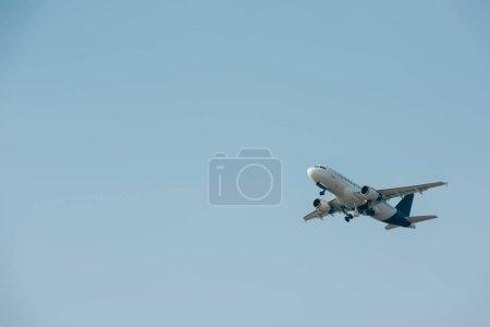 Photo pour Avion à réaction commercial décollant dans le ciel bleu avec espace de copie - image libre de droit