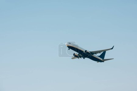 Low angle view of airplane departure in blue sky with copy space
