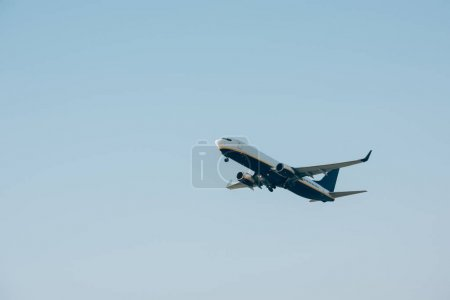 Photo pour Vue en angle bas de l'avion décollant dans un ciel dégagé - image libre de droit
