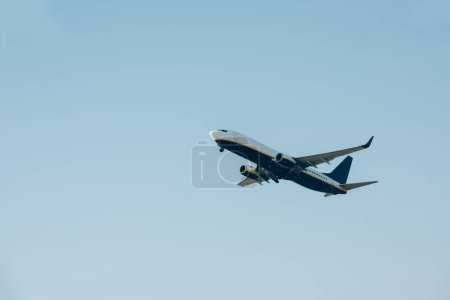 Photo for Low angle view of flight departure of airplane in blue sky - Royalty Free Image