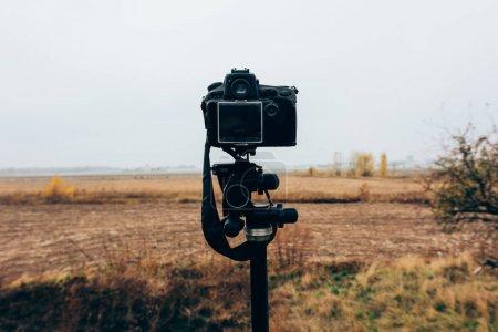 Photo pour Mise au point sélective de l'appareil photo numérique sur le trépied dans un champ herbeux - image libre de droit