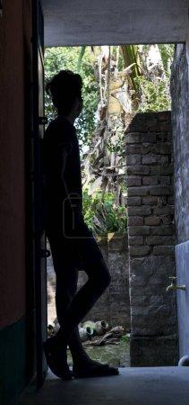 Photo pour Silhouette image d'un adolescent debout devant la porte et penché sur la porte et regardant à l'extérieur de la lumière du jour ensoleillée et la nature - image libre de droit