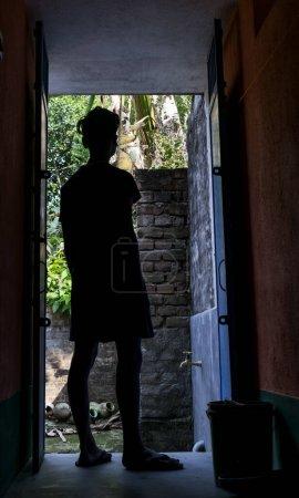 Photo pour Silhouette image d'un adolescent debout devant la porte et regardant à l'extérieur de la lumière du jour ensoleillée et la nature - image libre de droit