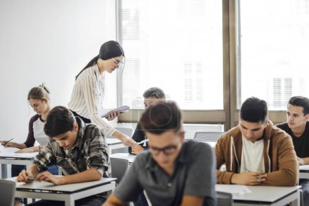 Photo for Group of high school students doing exam at classroom. - Royalty Free Image