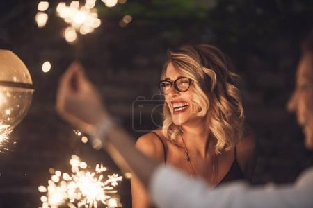 Photo for Beautiful blonde woman holding sparklers at party and smiling with her friends. - Royalty Free Image