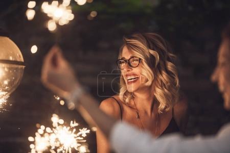 Photo pour Belle femme blonde tenant des étincelles à la fête et souriant avec ses amis . - image libre de droit