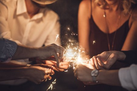 Photo for Hands of group of men and women holding sparklers at party. - Royalty Free Image