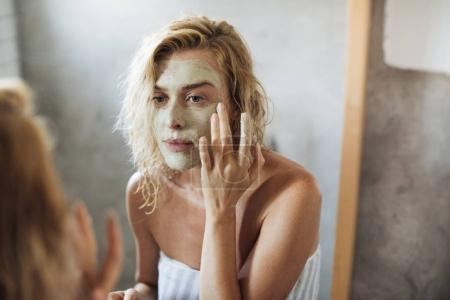 Photo for Beautiful blonde Caucasian woman standing in her bathroom and putting cosmetic mask on her face. - Royalty Free Image